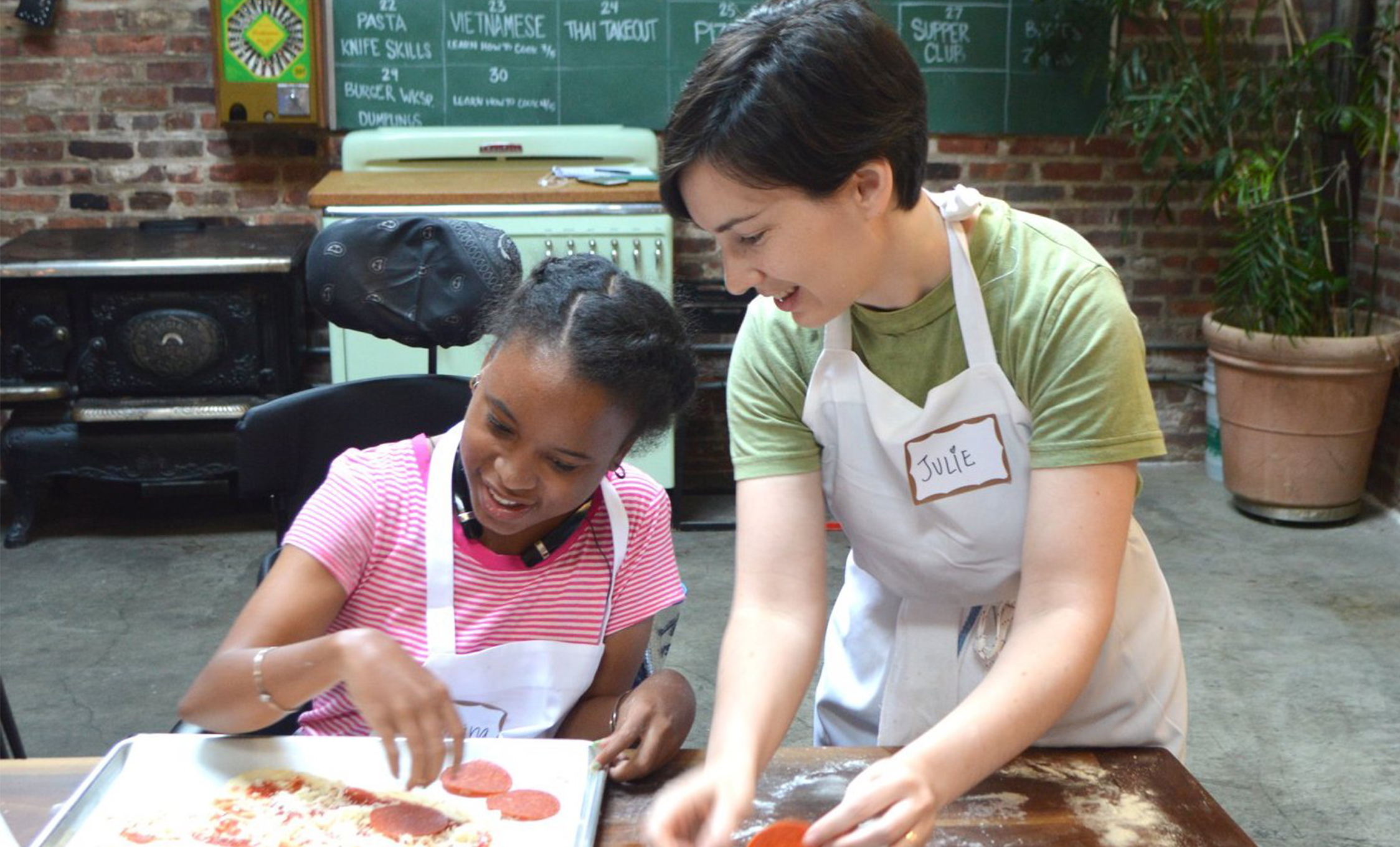 INCLUDEnyc volunteer is making pizza with an INCLUDEnyc youth