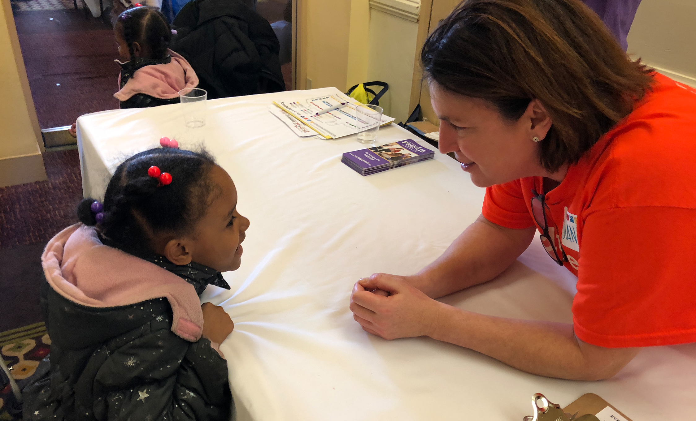 INCLUDEnyc's Diana Biagioli is bending down talking to a young girl